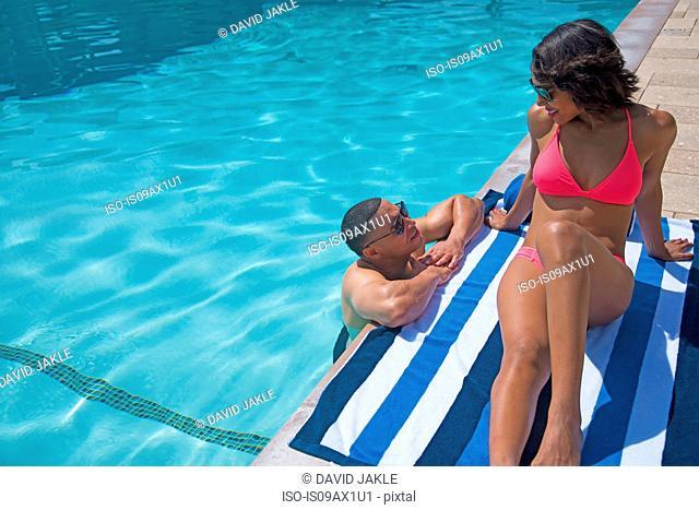 Couple chatting beside pool