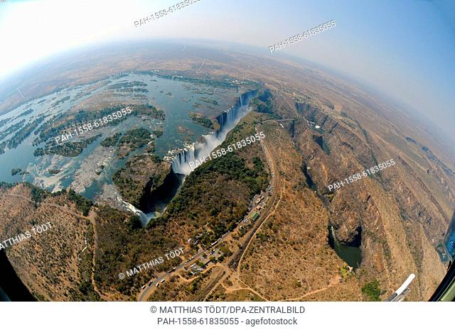 The course of the Victoria Falls, with the broad Zambezi River on the Zambian side to the left, the falls in the middle and the flow downriver in Zimbabwean...