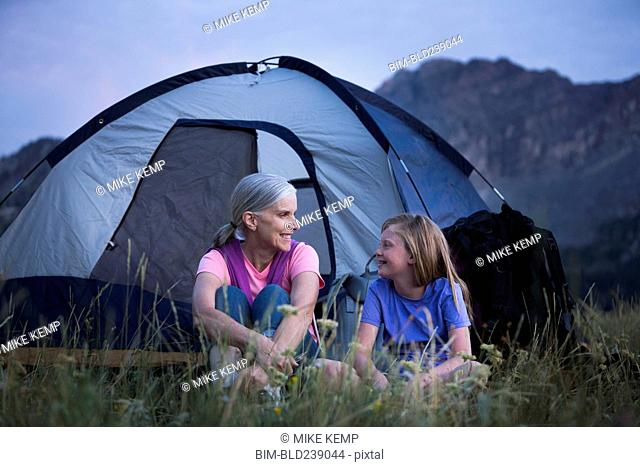 Caucasian grandmother and granddaughter camping on mountain