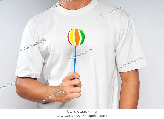 Mid section view of a man holding a lollipop