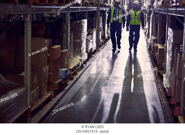 Workers walking along merchandise on shelves in distribution warehouse aisle