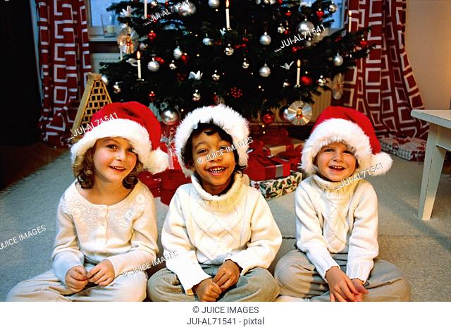Portrait of three young children in Santa Claus hats and their pajamas waiting for Santa