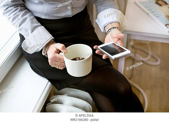 Midsection of businesswoman holding mobile phone and coffee cup in office