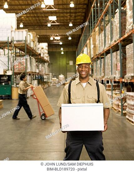 African male warehouse worker with box
