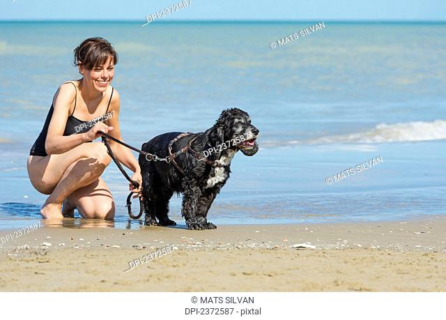 A Woman With Her Dog At The Beach; Rimini, Emilia-Romagna, Italy