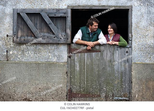 couple leaning on stable gate