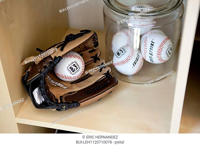 Close-up of baseball gloves with balls in jar on shelf; San Marcos; California; USA