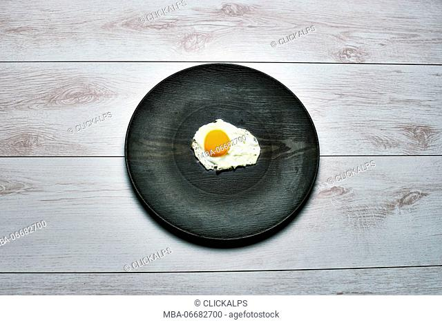 Top view of an egg and a black dish on a white wooden table