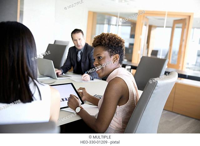 Smiling businesswoman using digital tablet in conference room meeting