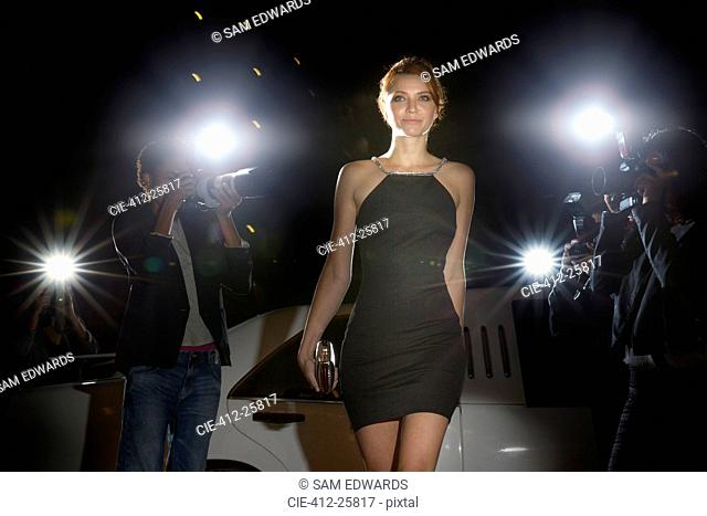 Celebrity in black dress arriving at event and being photographed by paparazzi