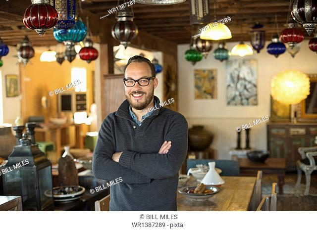 A man standing in a shop full of antique and decorative objects. Antique shop displays. Lighting, glass shades and furniture