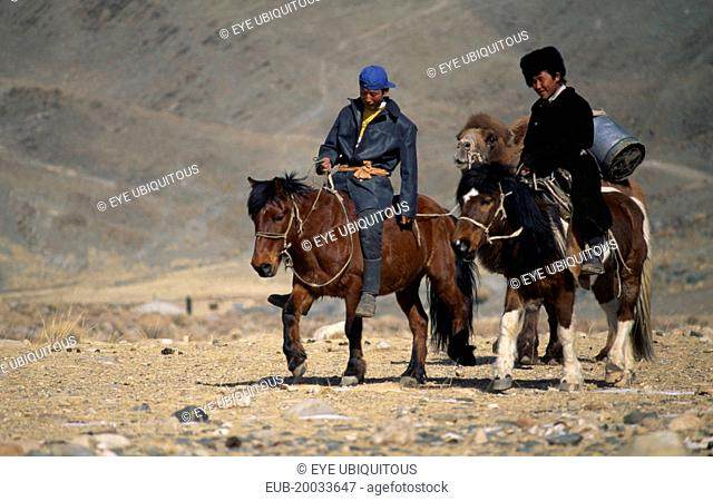 Kazakh men on their way to the Kazakh New Year festivities riding horses and leading pack camel