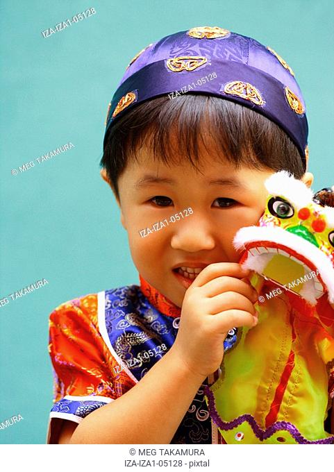 Portrait of a boy holding a toy
