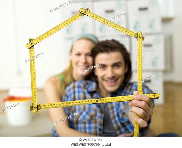 Young couple making house shape with folding rule, portrait