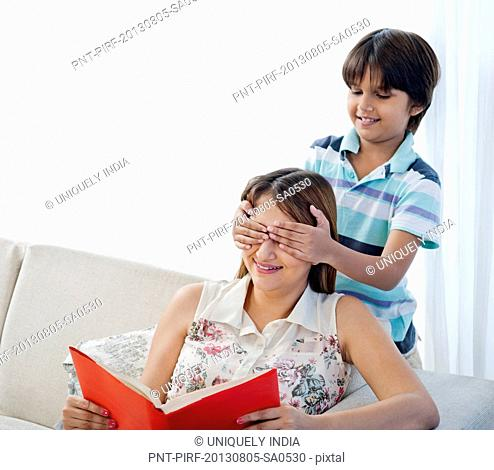 Boy covering eyes of his mother from behind