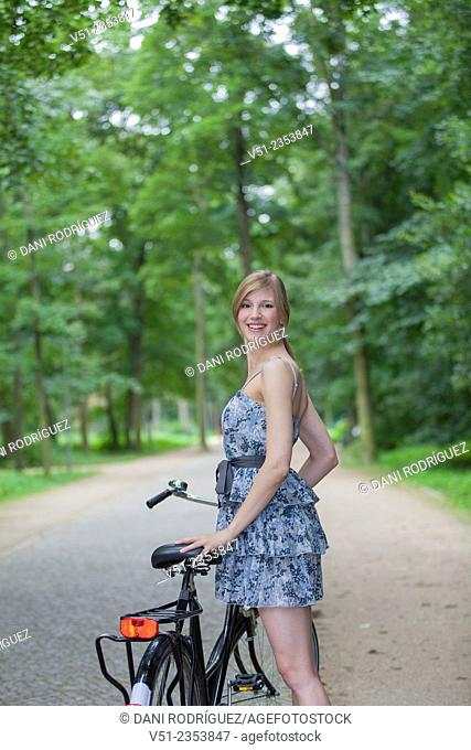 Happy blonde woman with bicycle in park smiling at camera