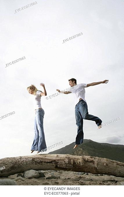 Carefree young couple jumping on a fallen log on the beach