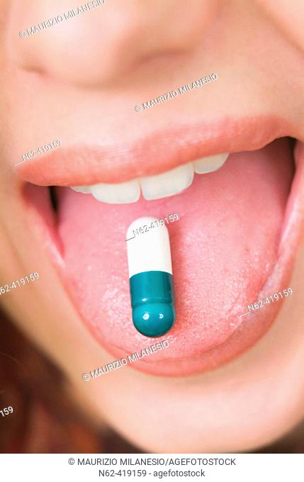 Pillon green and white resting on the tongue of a girl with open mouth