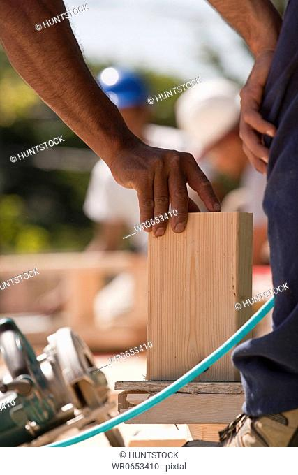 Carpenters positioning wood trim at a construction site