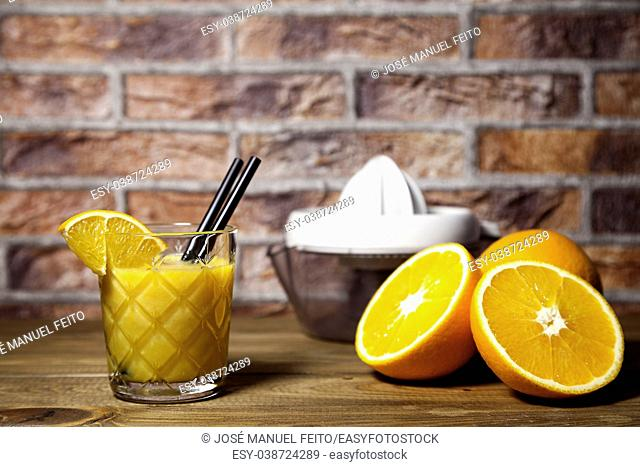 orange juice, natural orange and squeezer on wood table and brick background
