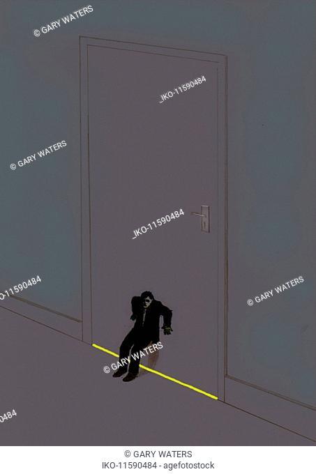 Businessman struggling in dark to keep door shut
