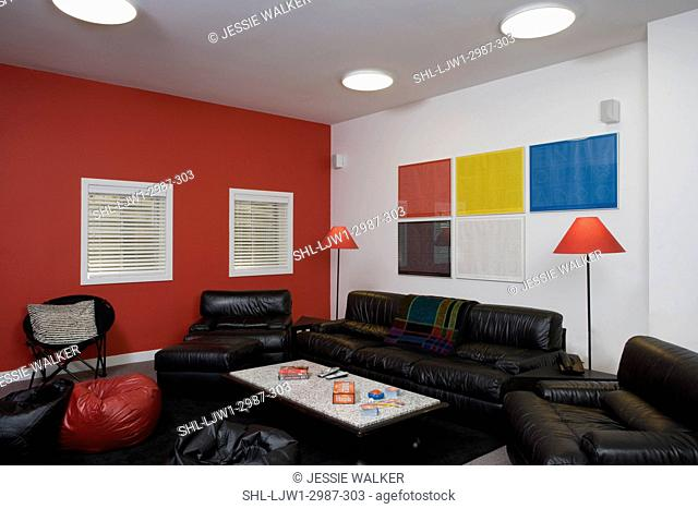 BASEMENTS: Media viewing area, black leather sofas and chairs, red wall, colorful print art, red shaded lamps