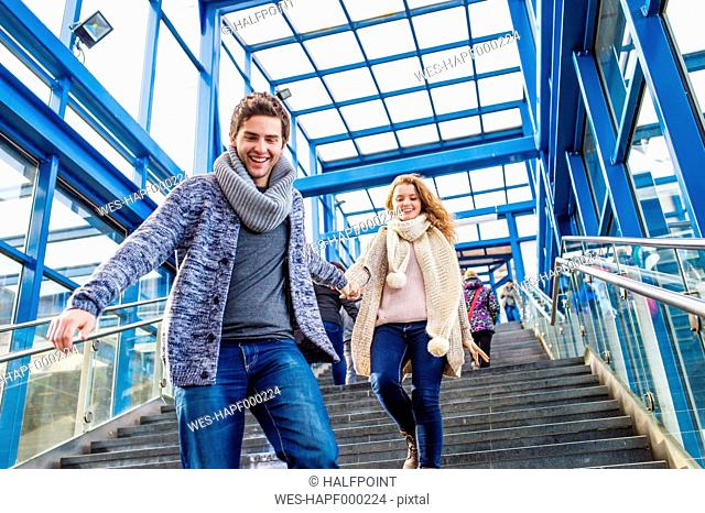 Young couple in a hurry running downstairs at train station