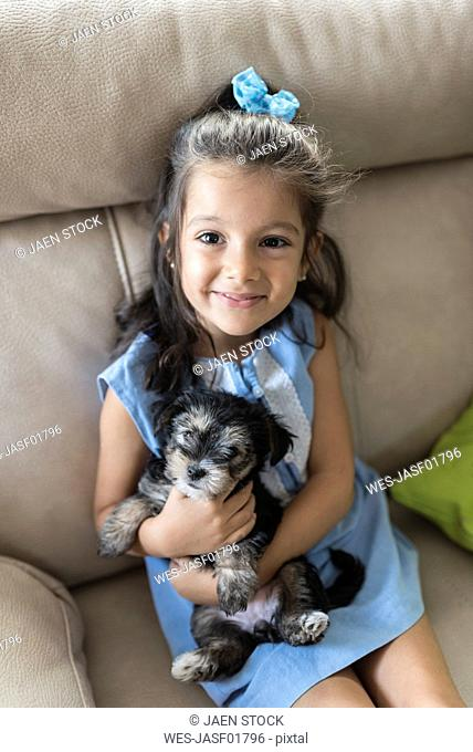 Portrait of happy little girl sitting on the couch with puppy on her lap