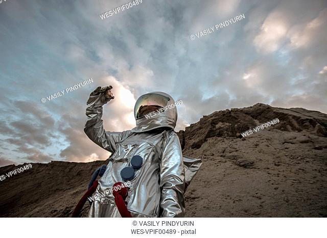 Spaceman on a nameless planet, taking rock samples
