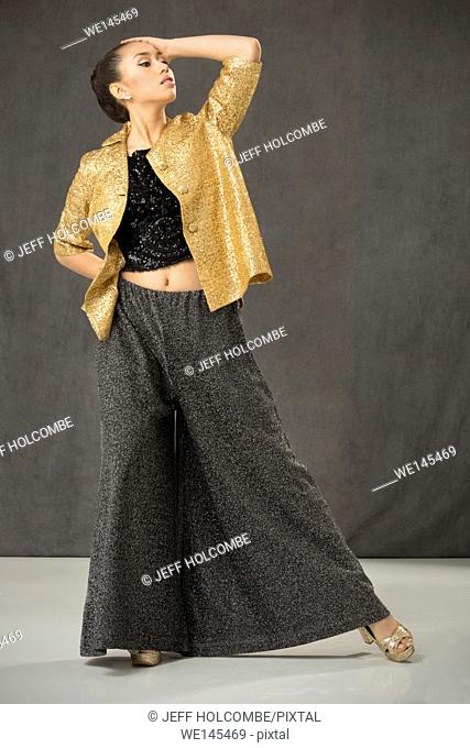 Young woman dancing in open gold jacket and baggy gray pants with white floor and gray background