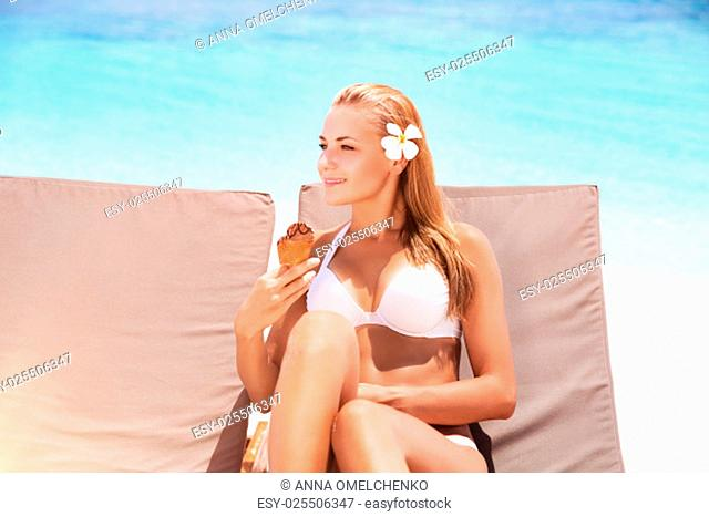 Beautiful woman on the beach, pretty girl sitting on sunbed with two ice cream in hand waiting for her boyfriend, enjoying summer vacation on tropical resort