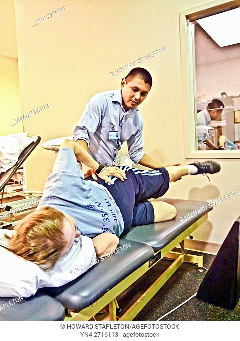 A physical therapist works on a patient following knee replacement surgery
