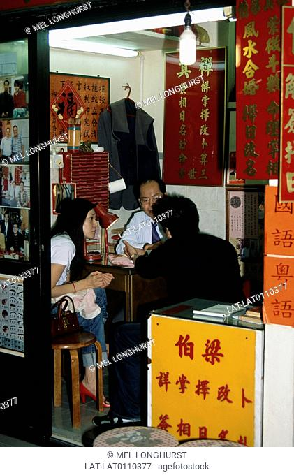 Fortune teller seated in booth with two people. Inscrptions on wall,photographs of clients. Wong Tai Sin