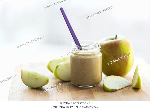 jar with apple fruit puree or baby food on table