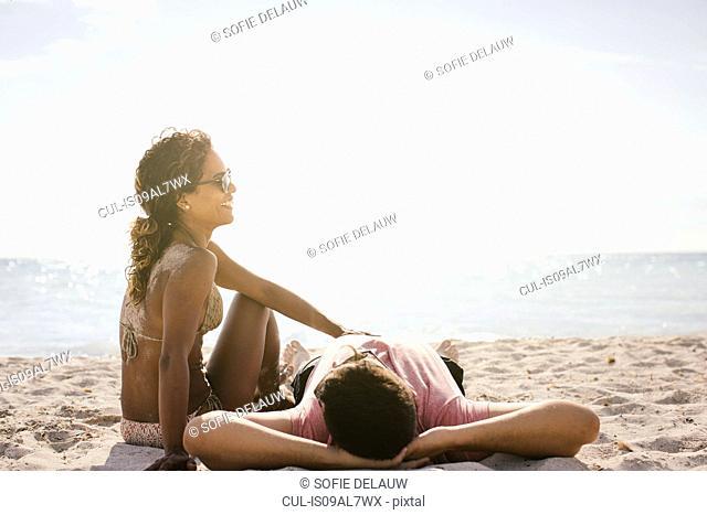 Couple on beach sunbathing, Tuscany, Italy