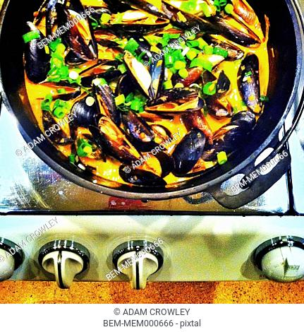 Pan of mussels and vegetables on stove