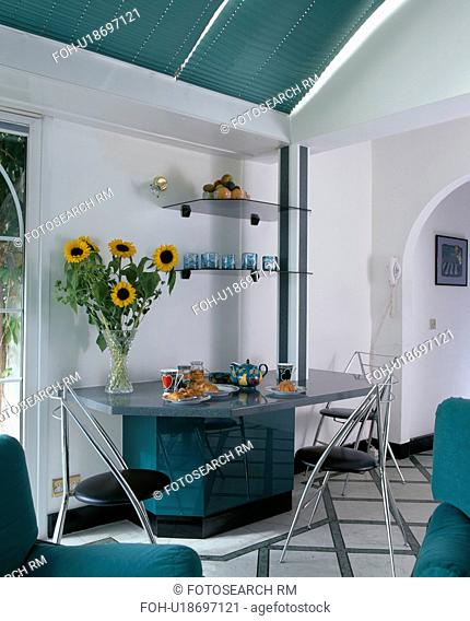 Vase of sunflowers on fitted granite table set for breakfast in modern white dining room with glass shelves