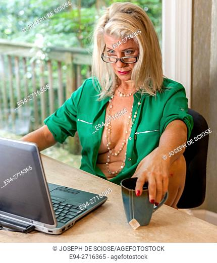 A partially nude and pretty 52 year old blond woman sitting at a table with laptop computer