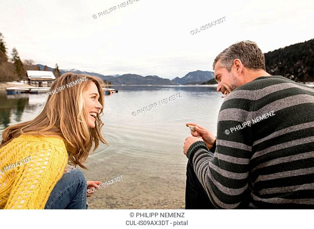 Couple crouching beside lake, smiling, German Alps, Germany