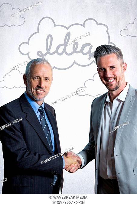 Business men shaking hands against white wall with idea doodles