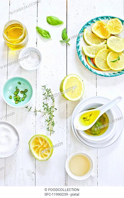Italian vinaigrette and ingredients on a white wooden table