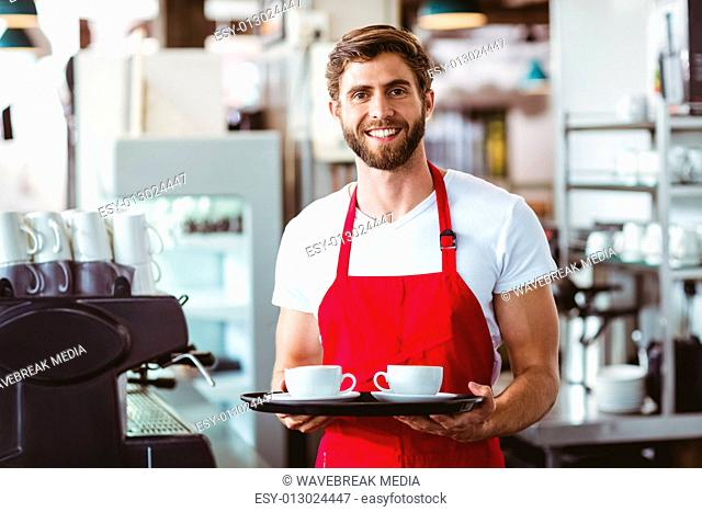 Handsome barista holding two cups of coffee