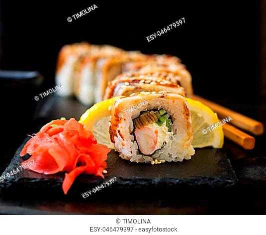 Traditional Japanese food - sushi, rolls and sauce on a black background