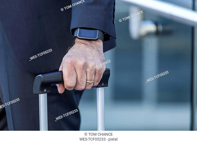 Close-up of businessman with smartwatch and trolley bag