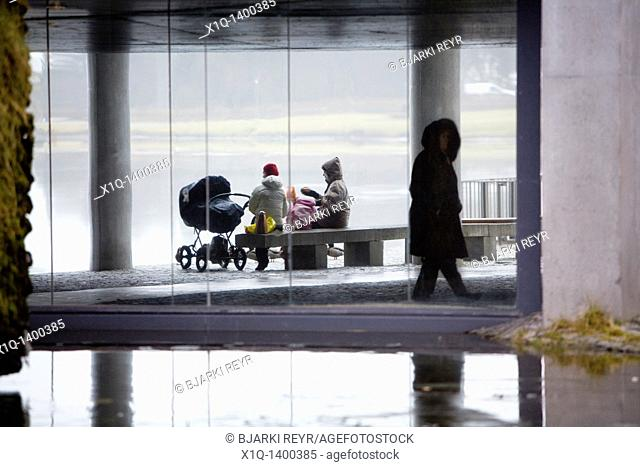 A family enjoying a picnic outside during a rainy, foggy day  Person walking by  Reykjavik City Hall, downtown Reykjavik, Iceland