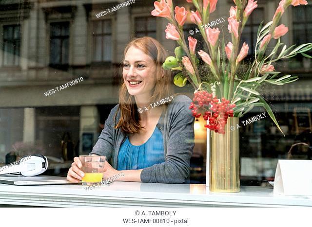 Portrait of happy woman sitting in a coffee shop looking through window