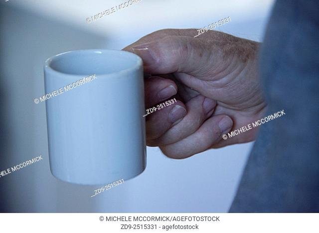 An older man holds his coffee cup