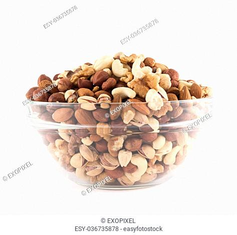Almond, pistachio, peanut, walnut, hazelnut mixed in a glass bowl isolated over white background