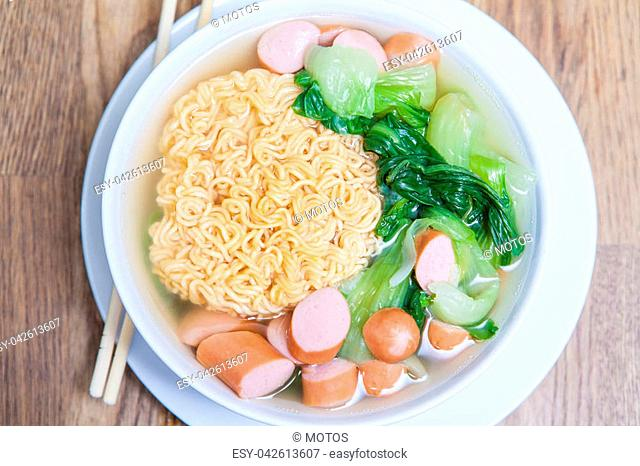 Instant Noodles with sausage with Pak Choy or Chinese Cabbage in white bowl and Plate on wooden table