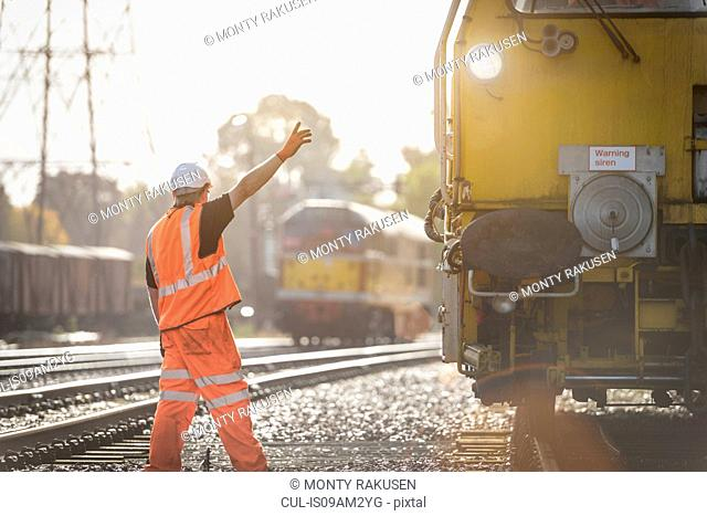 Maintenance worker signalling to train on railway
